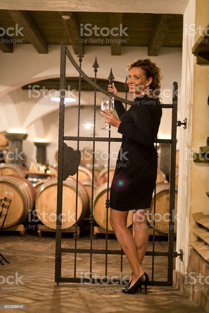 Happy Female Vintner Tasting White Wine, Old Cellar in Europe stock photo