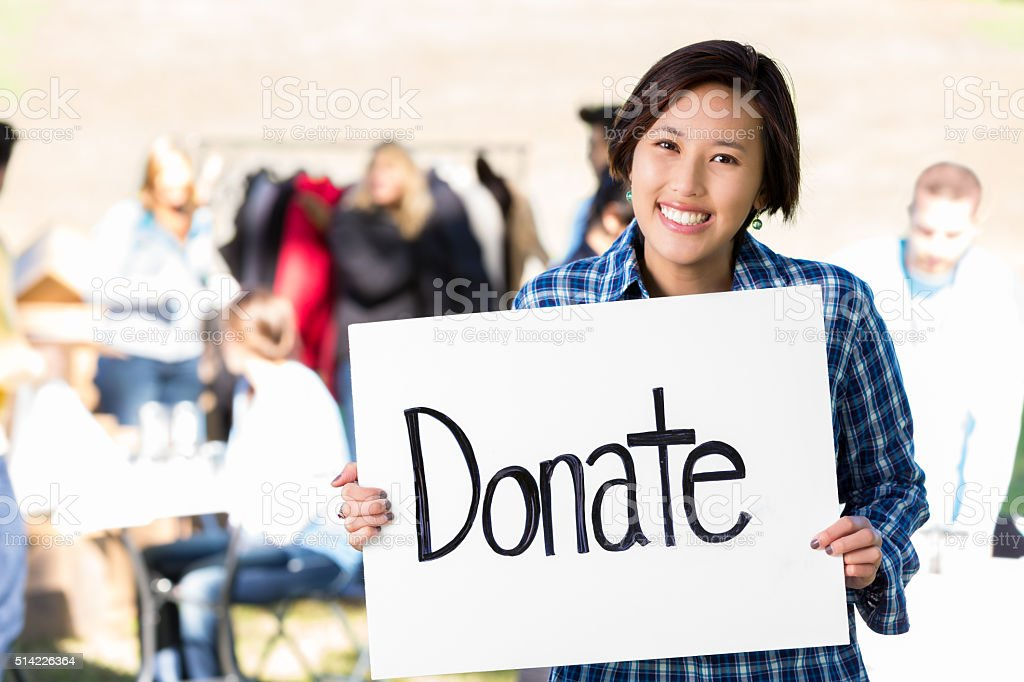 Happy female volunteer at clothing drive stock photo