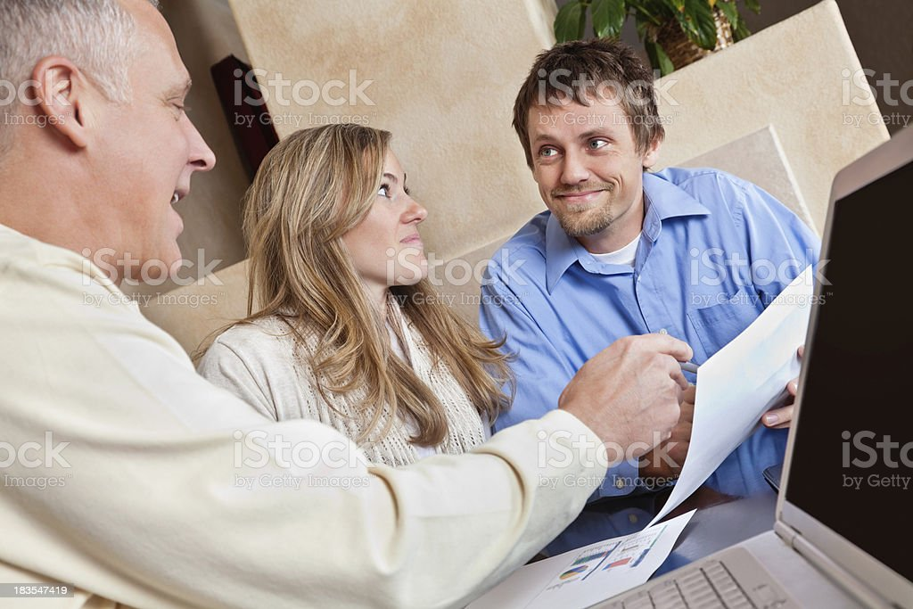 Happy Financial Advisor Talking About Finances to Couple royalty-free stock photo