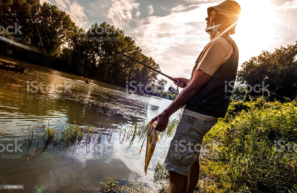 Happy fisherman caught a fish on the river. stock photo
