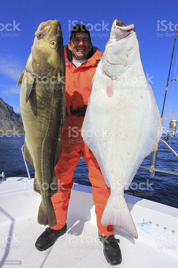 Happy fishermen with cod and halibutt stock photo