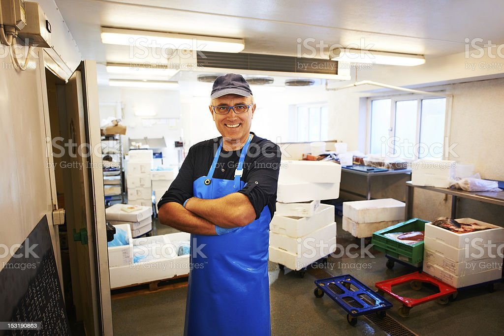Happy fishmonger in his workplace stock photo