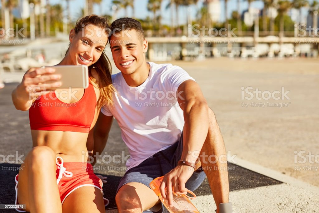 Happy fit couple taking selfie at beach stock photo