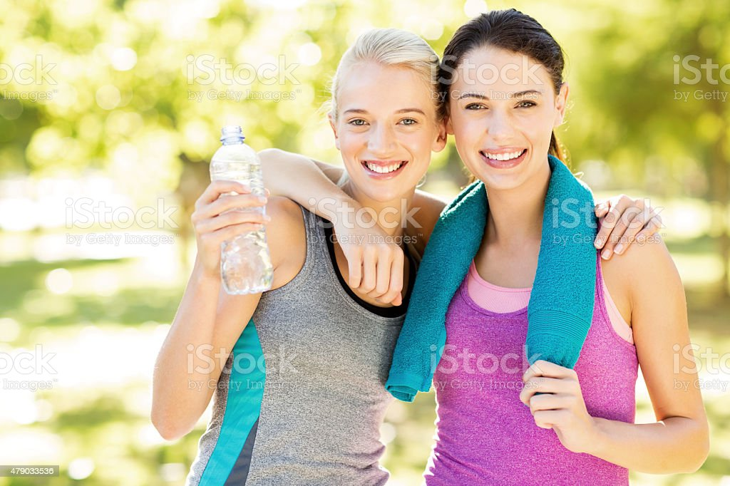 Happy Fit Friends Standing Arms Around In Park stock photo