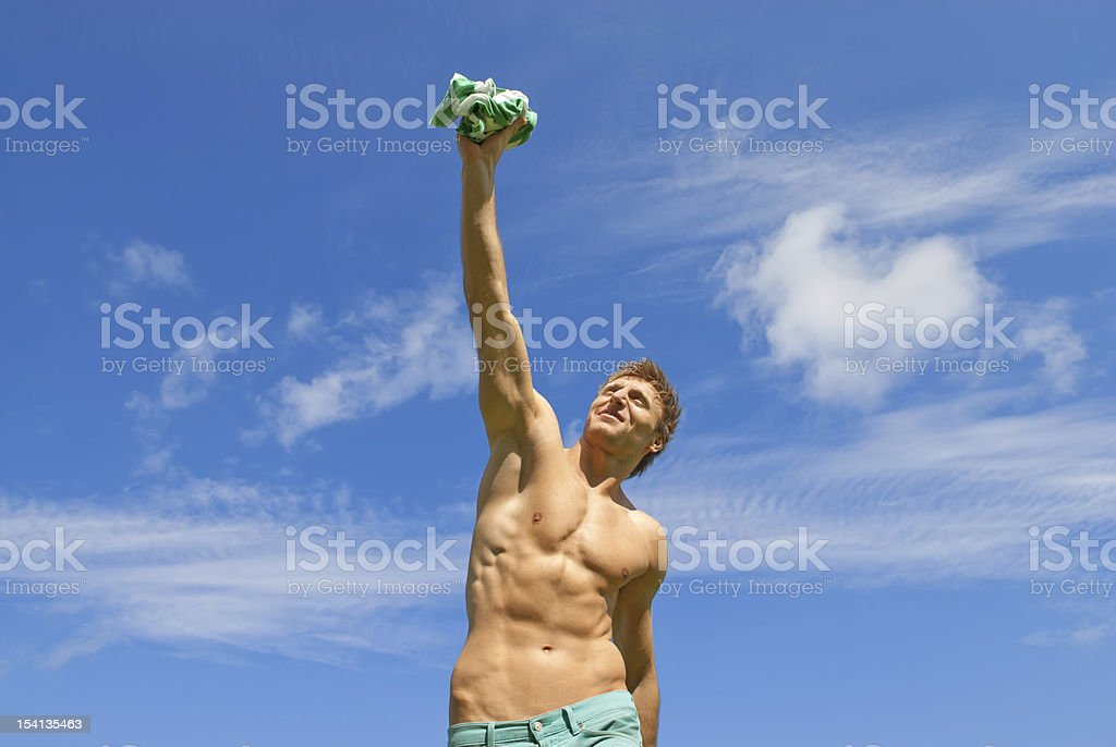 Happy fit guy holding his t-shirt royalty-free stock photo