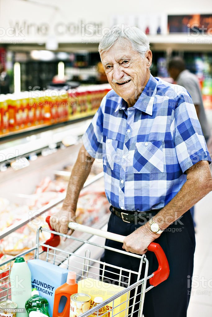 Happy , fit looking senior man shopping in supermarket stock photo