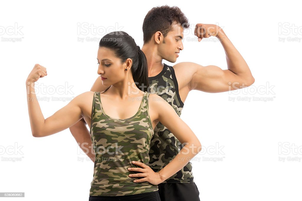 Happy fitness trainers posing with biceps stock photo