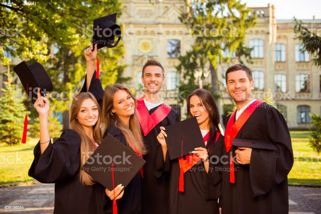 happy five graduates in robes holding mortar-board with tassel stock photo