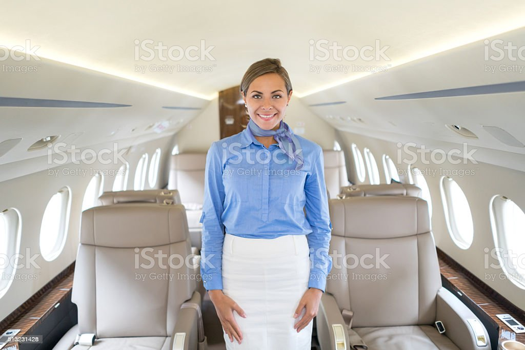 Happy flight attendant in an airplane stock photo