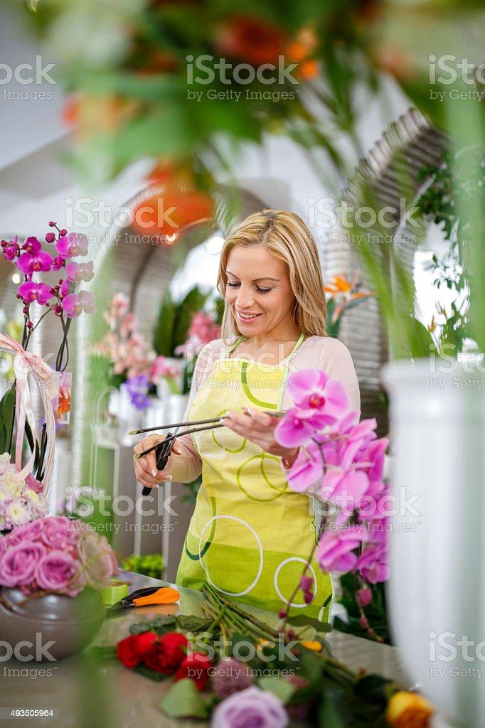 Happy florist making orchid bouquet in flower shop. stock photo
