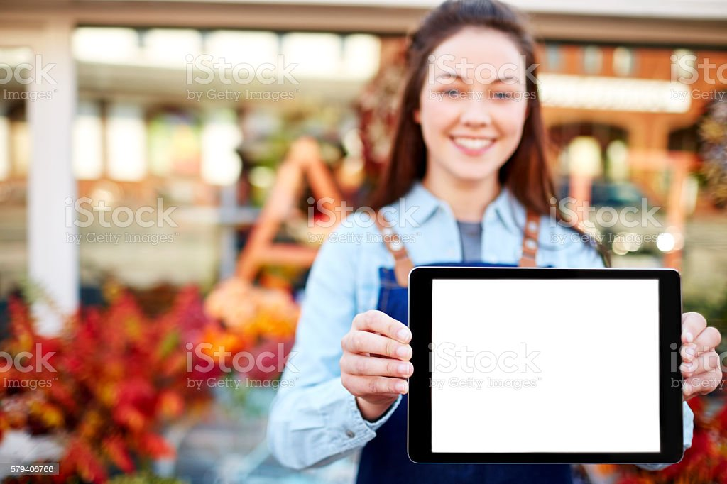 Happy florist showing digital tablet with blank screen stock photo