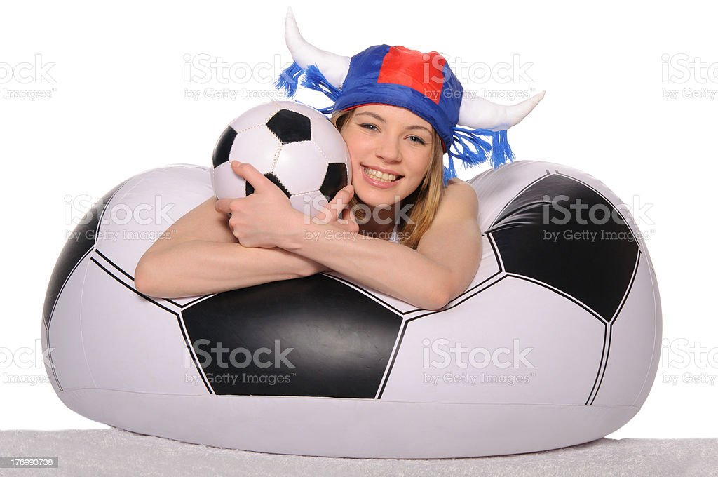 Happy football cheerleader with ball on couch royalty-free stock photo