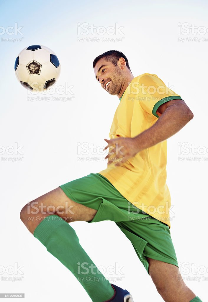 Happy football player kneeing the ball against clear sky stock photo