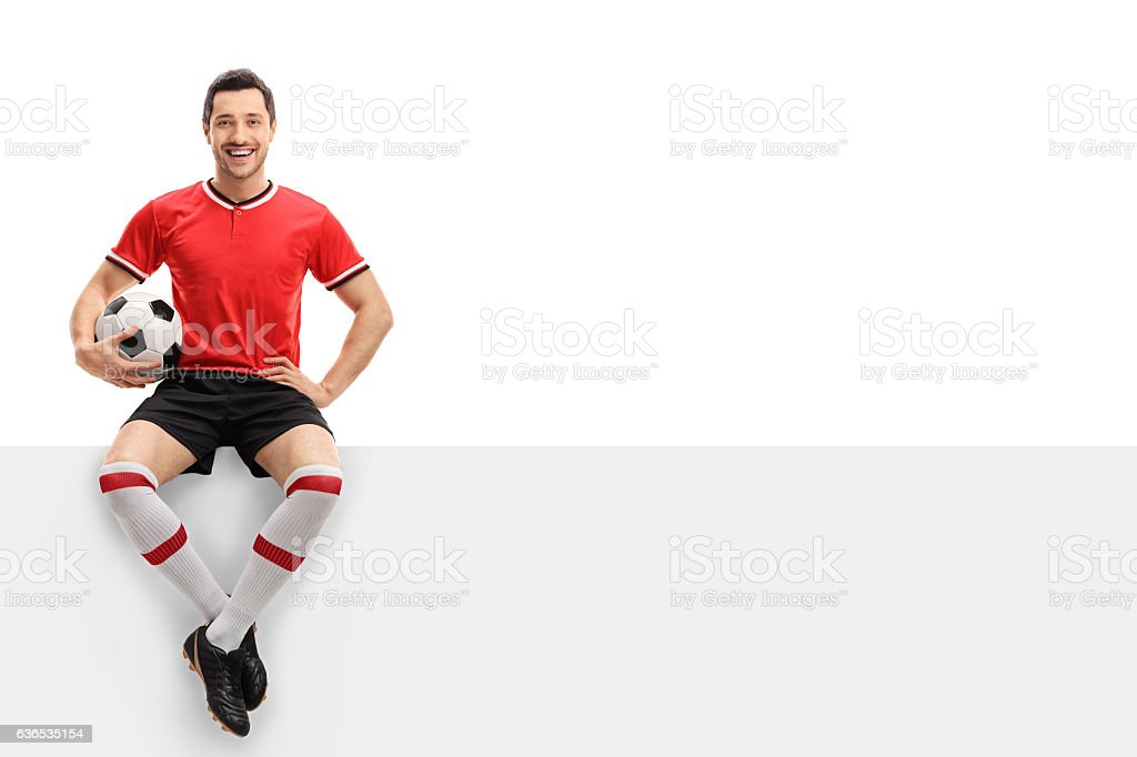 Happy football player sitting on a panel stock photo