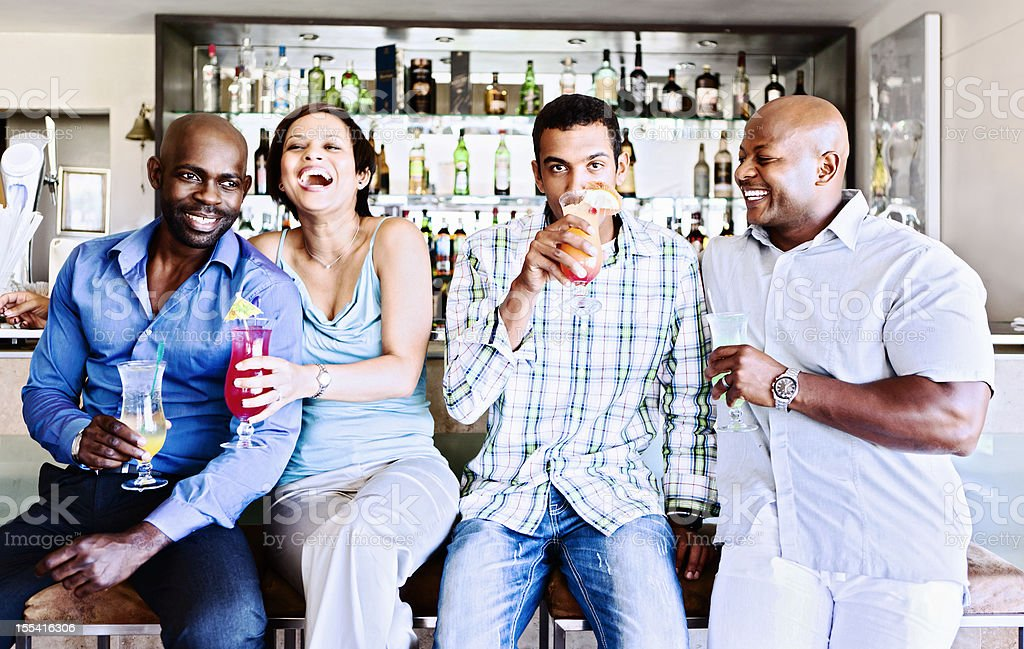 Happy foursome socializing in hotel bar stock photo