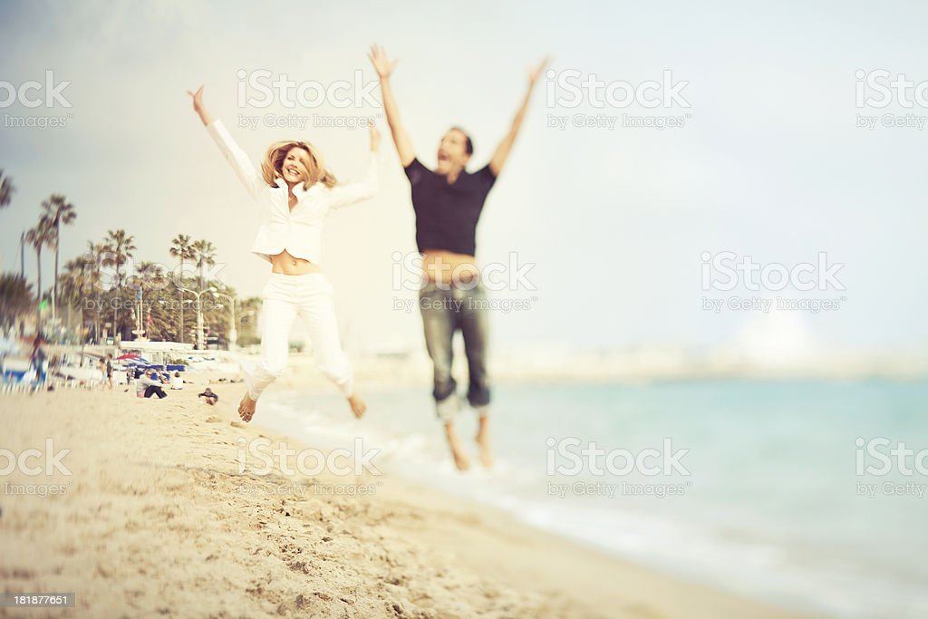 Happy French couple jumping on the beach in Cannes royalty-free stock photo