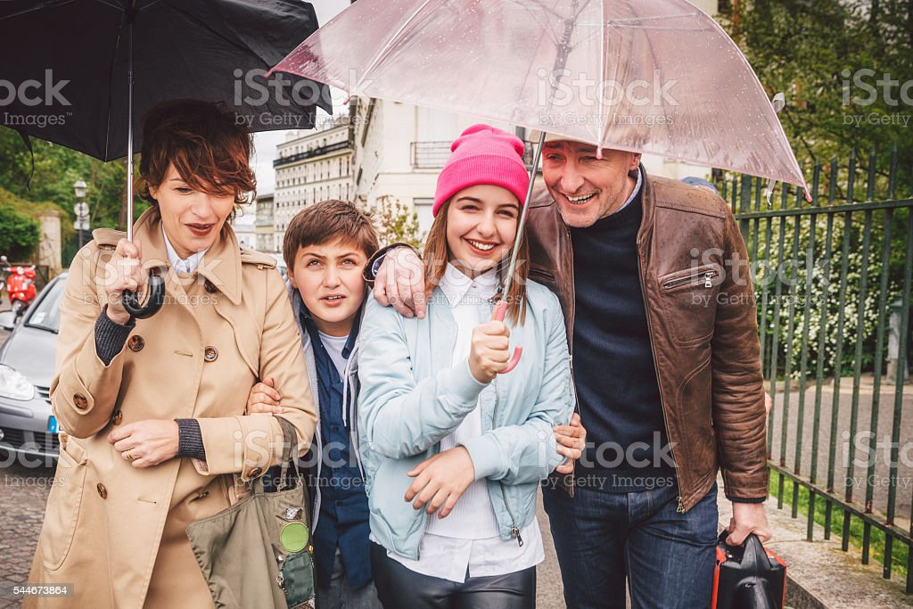 Happy french family out in the rain stock photo