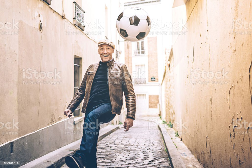 happy french man playing soccer in Paris street stock photo