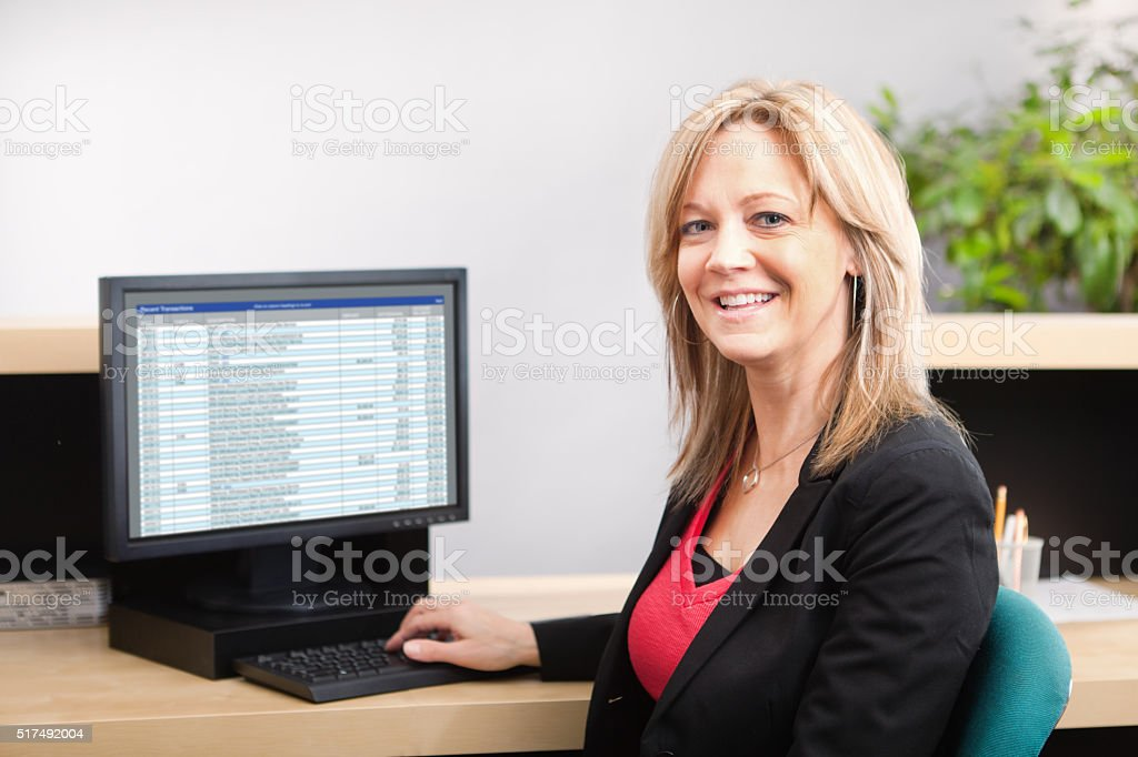 Happy Friendly Bank Teller in Retail Banking Counter stock photo