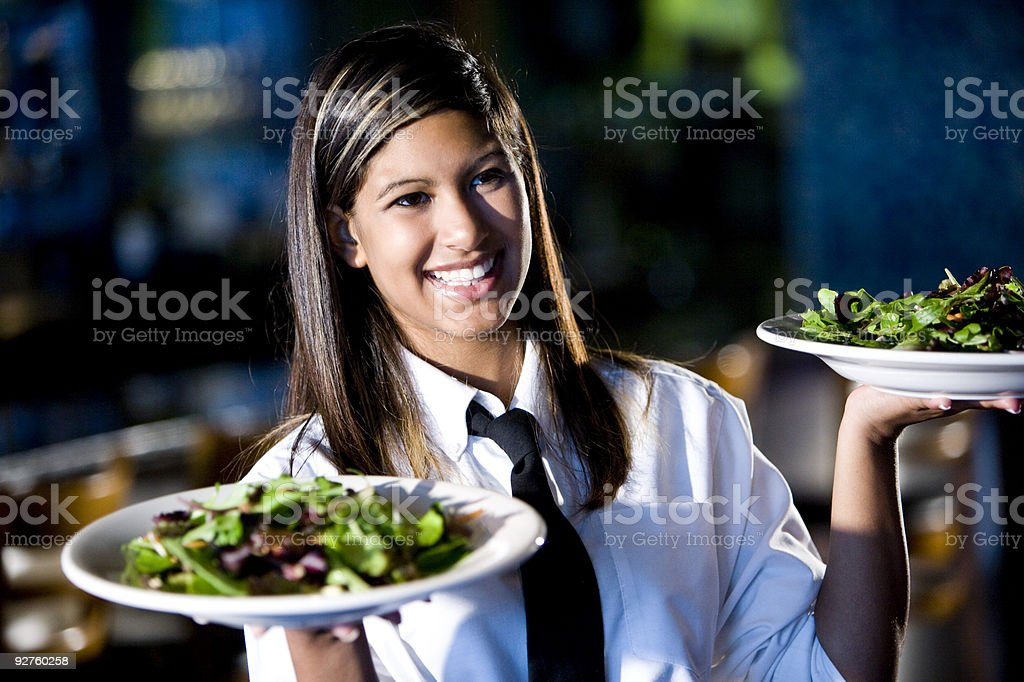 Happy friendly hispanic waitress serving salads stock photo