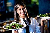 Happy friendly hispanic waitress serving salads