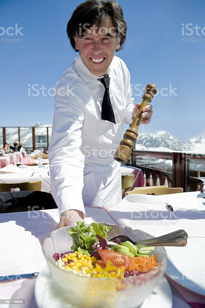 Happy friendly waiter serving salad stock photo