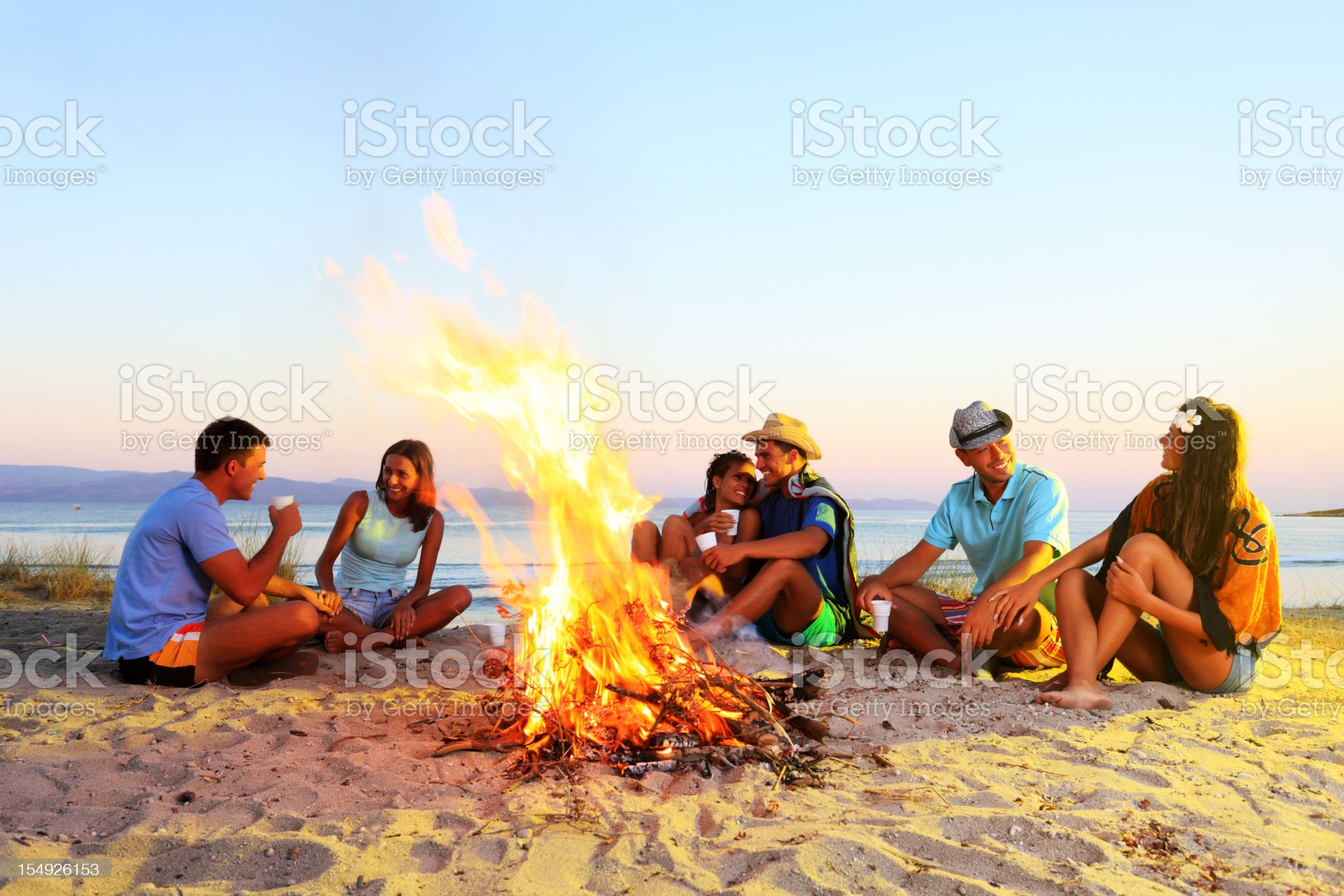 Happy friends are enjoying, sitting next to the campfire. royalty-free stock photo