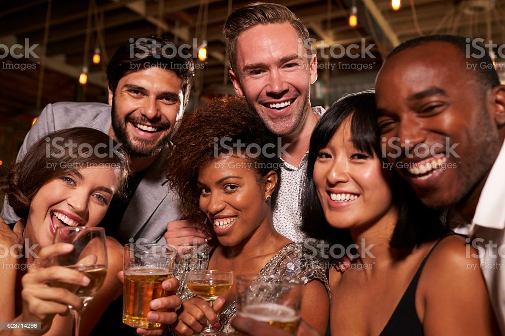 Happy friends at a party in a bar look to camera, stock photo