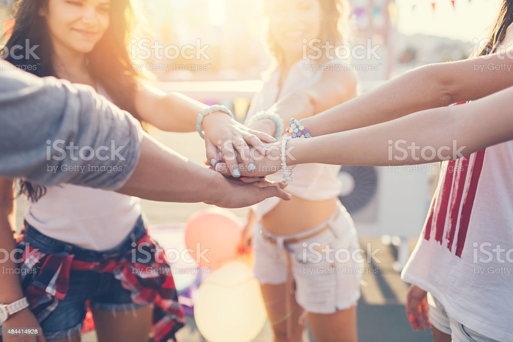 Happy friends at the rooftop putting hands together stock photo