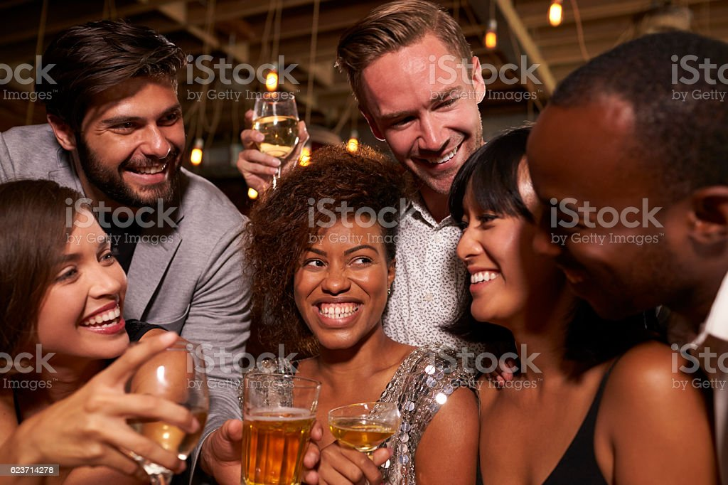 Happy friends celebrating at a party in a bar, close up stock photo