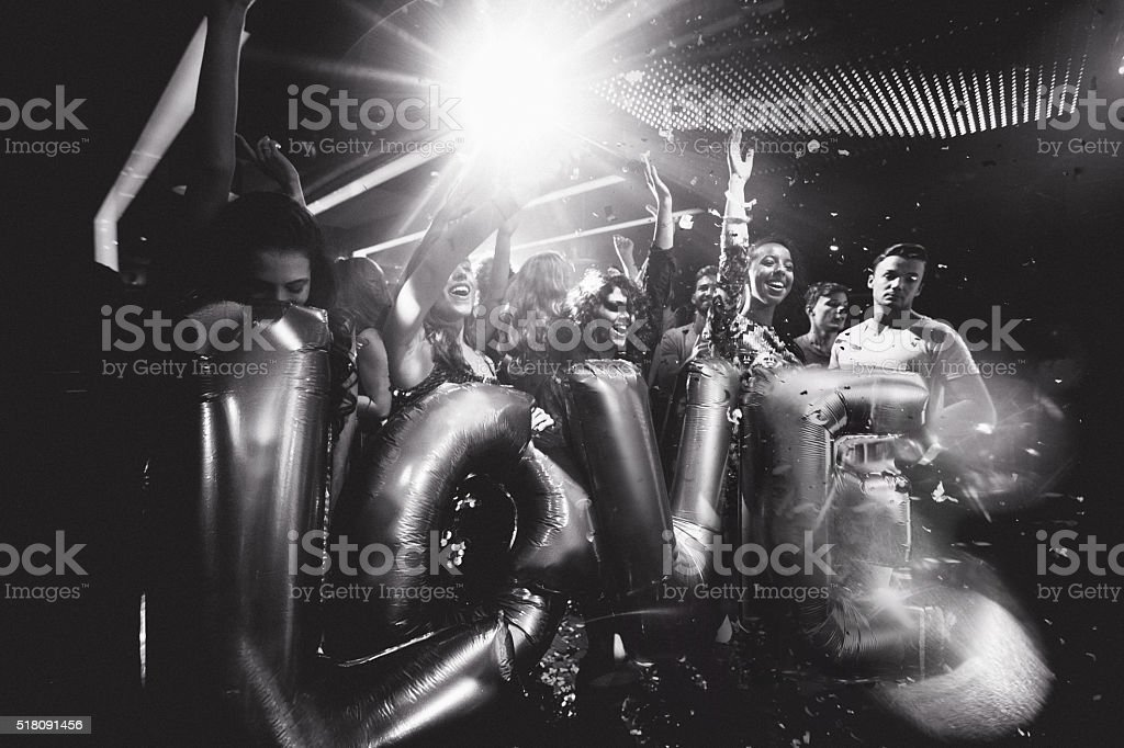 Happy friends celebrating night club party with ballons stock photo