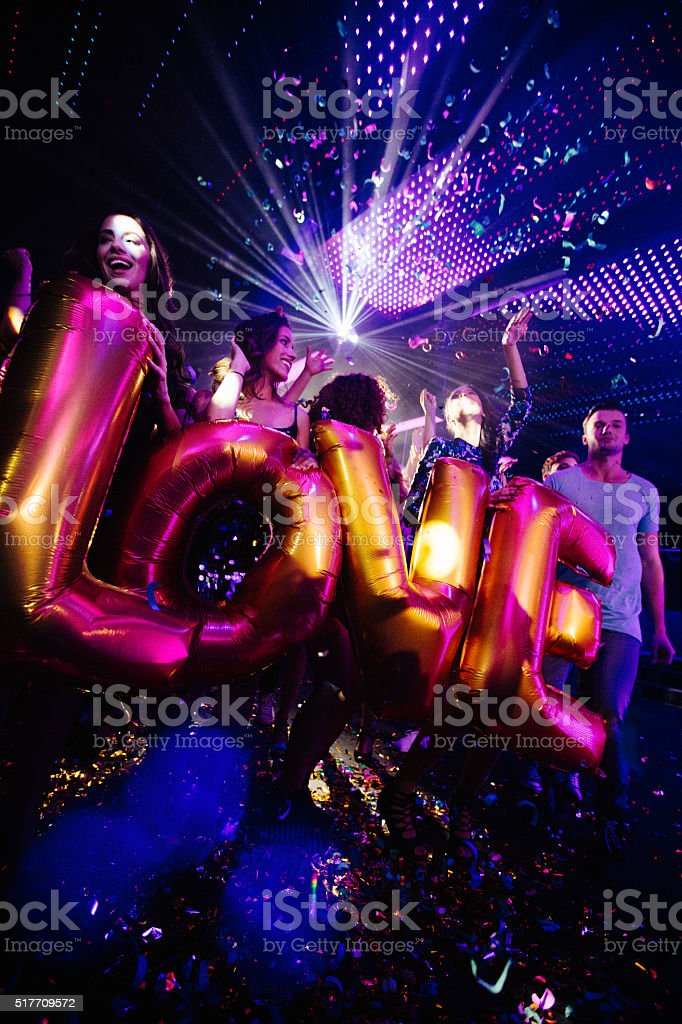 Happy friends celebrating night club party with confetti and ballons stock photo