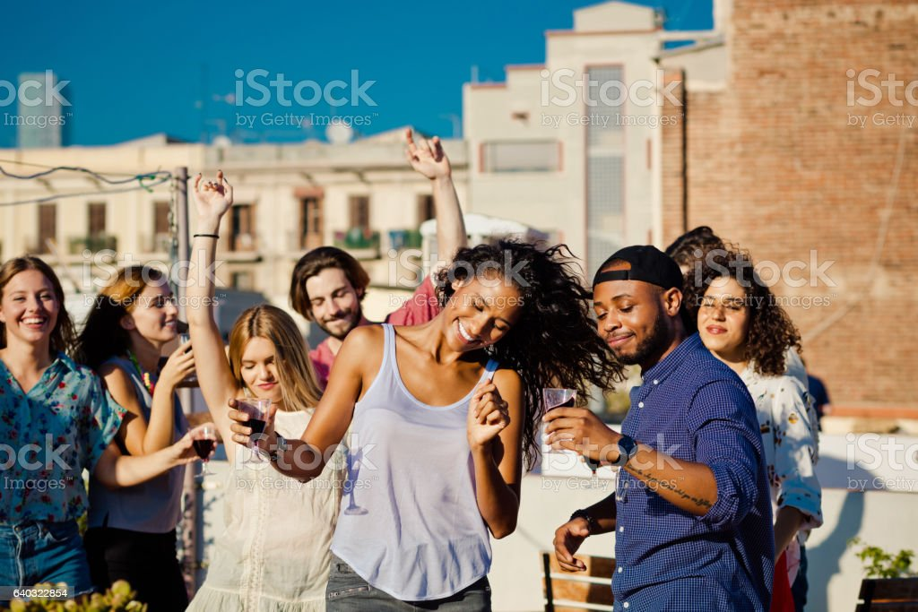 Happy friends dancing and drinking wine at rooftop party stock photo