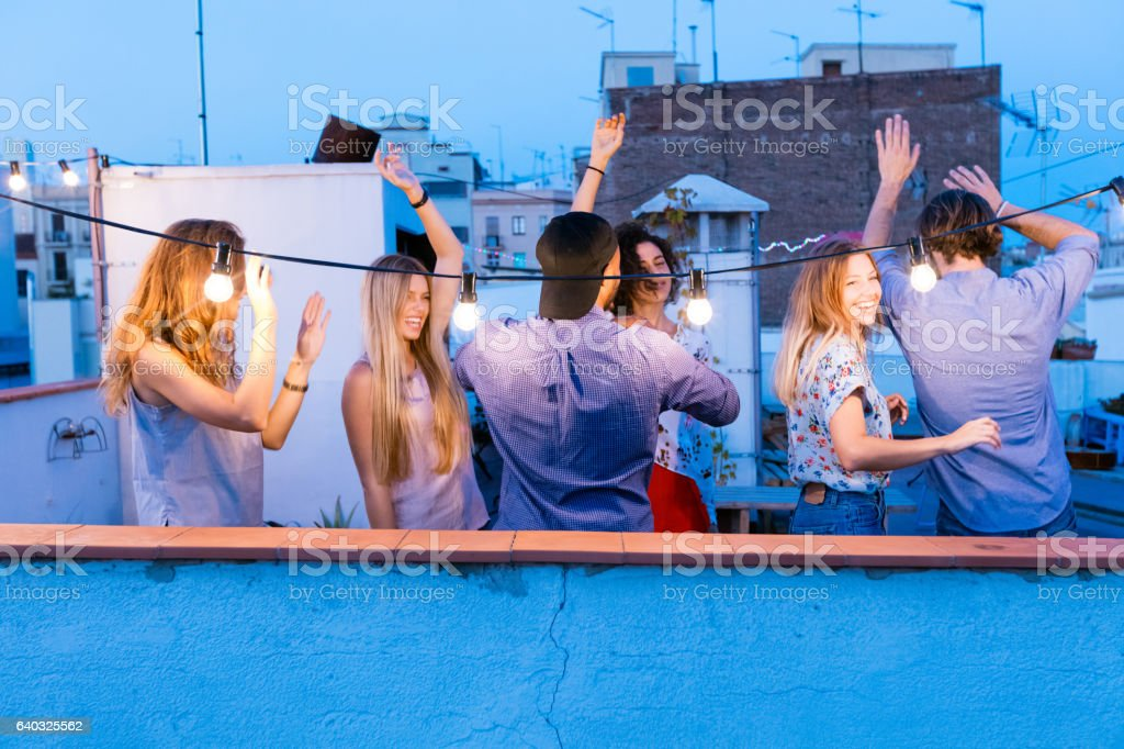 Happy friends dancing at the rooftop party stock photo