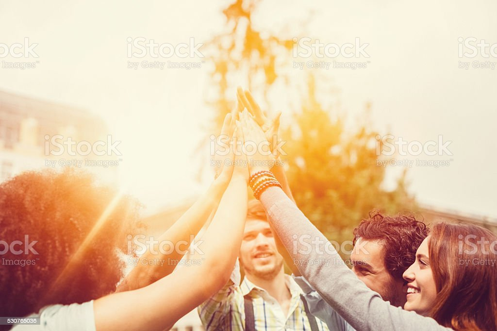 Happy friends doing high five stock photo