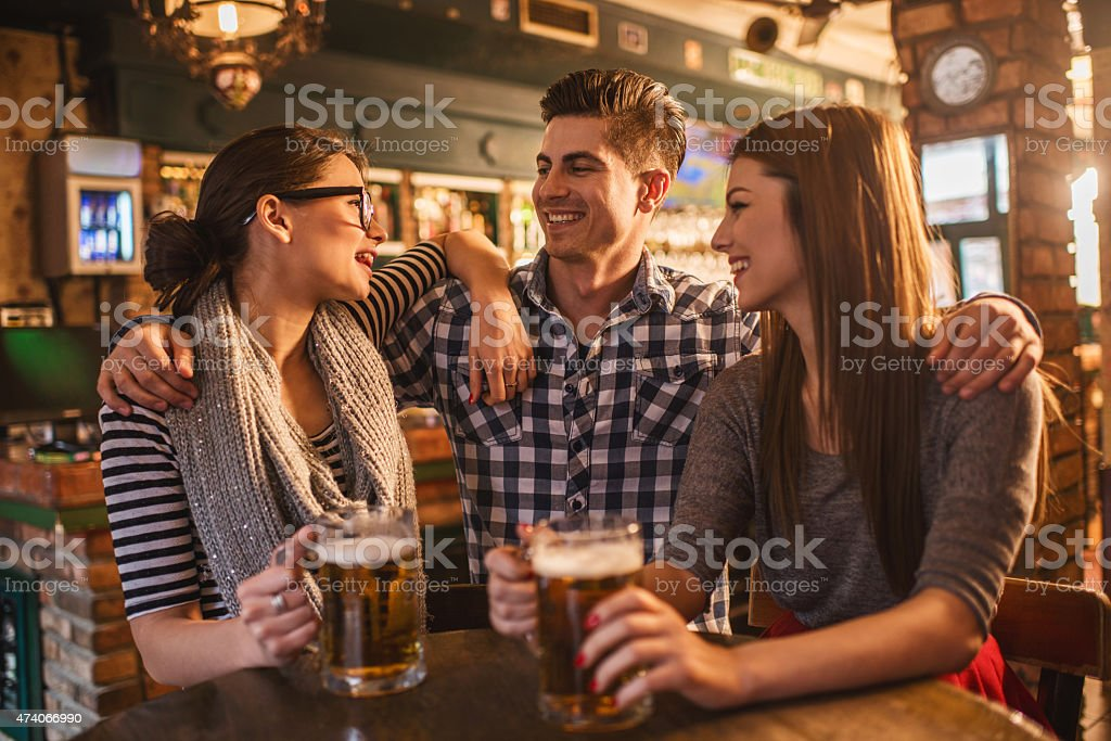 Happy friends drinking beer and having fun in a bar. stock photo