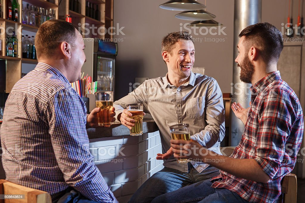 Happy friends drinking beer at counter in pub stock photo