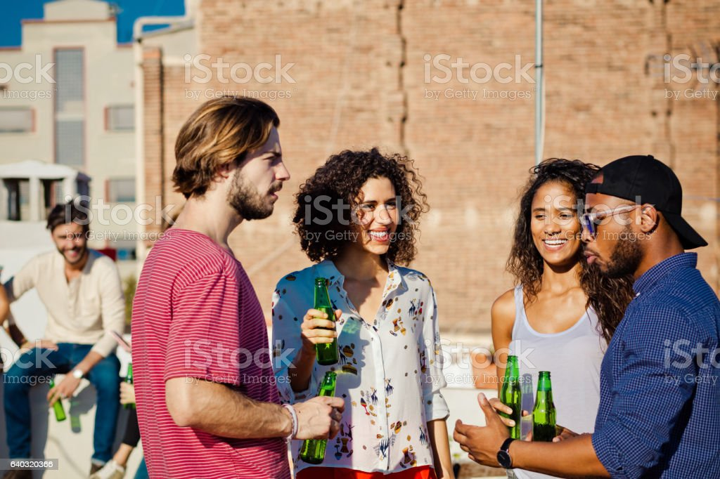Happy friends drinking beer at rooftop party stock photo