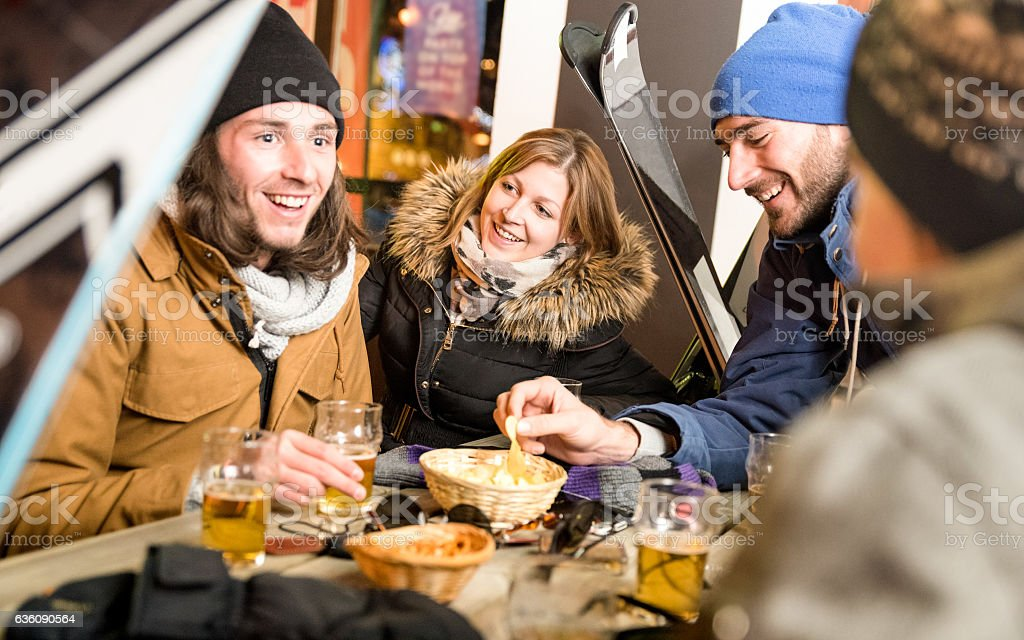 Happy friends drinking beer having fun at ski resort chalet stock photo