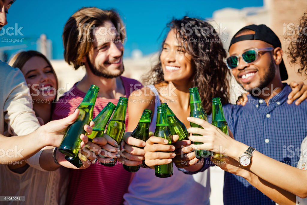 Happy friends drinking beer outdoors stock photo