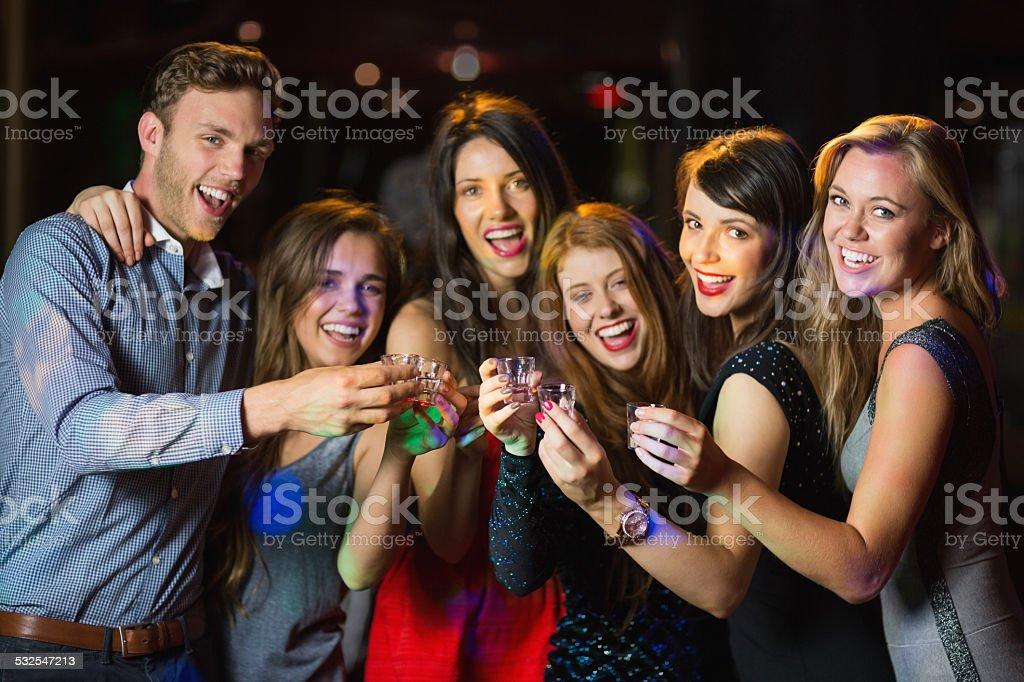 Happy friends drinking shots smiling at camera stock photo