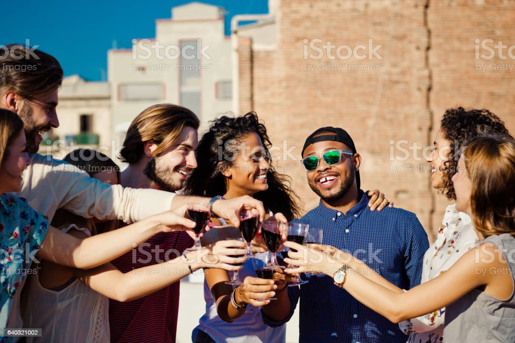 Happy friends drinking wine at rooftop party stock photo