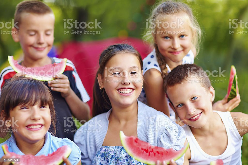 happy friends eating watermelon, outdoors stock photo