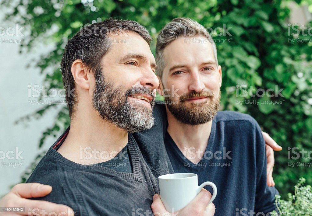 Happy friends embracing each other stock photo