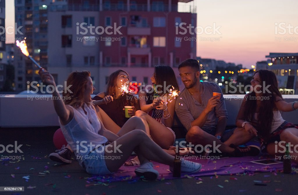 Happy friends enjoying a rooftop party stock photo