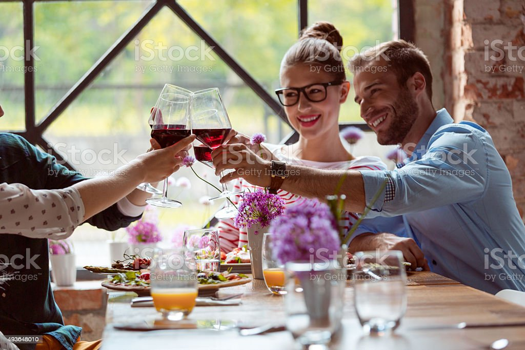 Happy friends enjoying dinner, toasting with red wine stock photo
