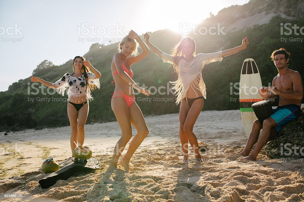 Happy friends enjoying on the beach and dancing stock photo