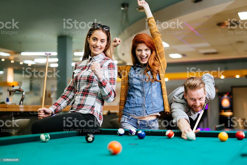 Happy friends enjoying playing pool stock photo