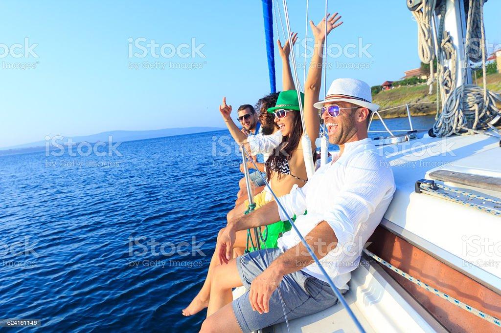 Happy friends enjoying travel with yacht stock photo