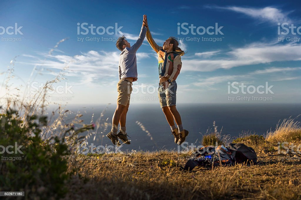 Happy friends giving high-five on hill against sea stock photo